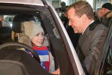 BMWの新車に乗り込むアリーナ・ザギトワ選手。右はメドベージェフ首相=モスクワ