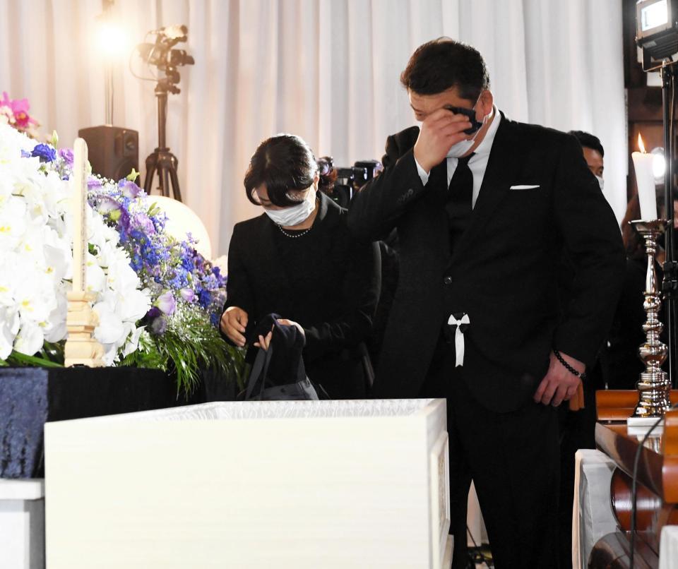 棺を前に涙をぬぐう吉田秀彦氏(右)=代表撮影