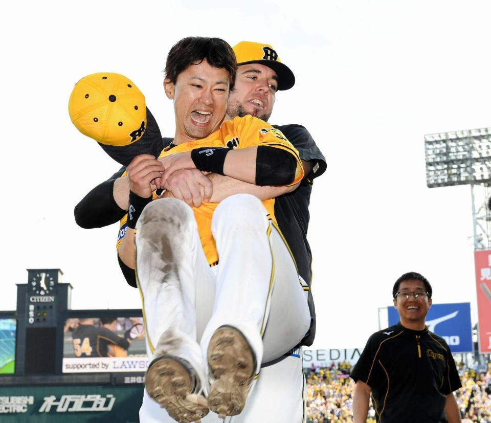 試合後、阪神・メッセンジャーに抱きかかえられ笑顔を見せる阪神・上本=甲子園(撮影・田中太一)